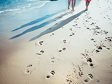 A beach with footprints and the shadows of three people